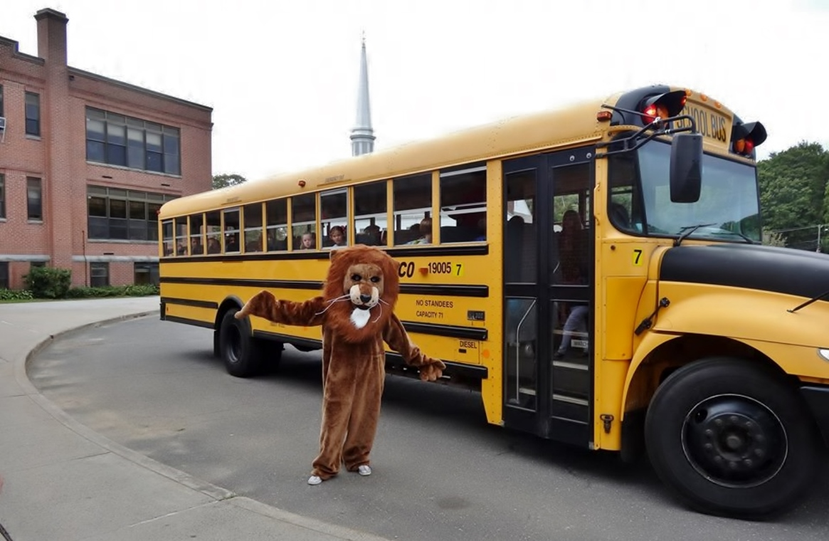 Mascot next to school bus